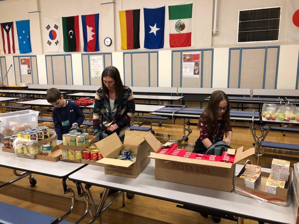 volunteers pack bags of food